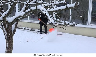 man clean snowy path with shovel along house wall in winter....