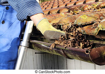 Cleaning a rain gutter - Man Cleaning a rain gutter in Close...
