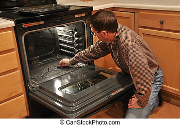 Man Cleaning An Oven - A man kneeling on the kitchen floor...