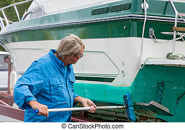 man cleaning boat with brush