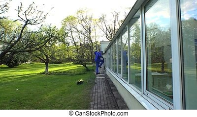 Man cleaning building exterior with high pressure water jet.