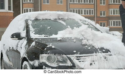 Man cleaning car from snow - Caucasian man is cleaning black...