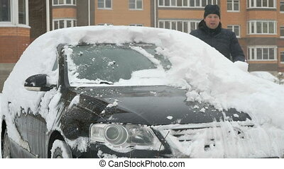 Man cleaning car from snow - Caucasian man in casual clothes...
