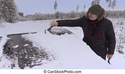Man cleaning car with brush in winter
