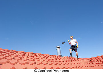 Man cleaning chimney on tiled roof