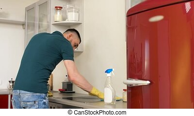 man cleaning cooker at home kitchen - household and people...