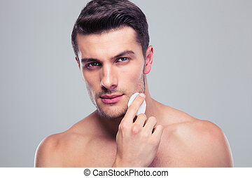 Man cleaning face skin with batting cotton pads over gray...
