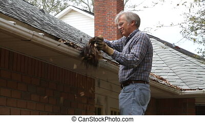 Man Cleaning Gutter - Mature adult man wearing gloves cleans...