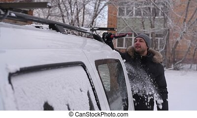 Man cleaning his car after the snowfall