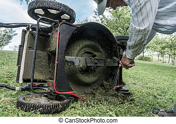 Man cleaning lawn mower blade.