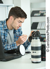 man cleaning lens of his digital camera with special brush