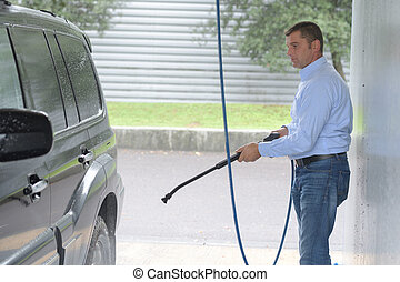 Man cleaning mpv with pressure washer