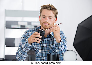 man cleaning photographic lense
