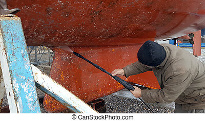 Man cleaning the bottom of a sailboat with high pressure water