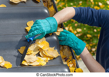 Man standing on the ladder and cleaning the roof from autumn leaves