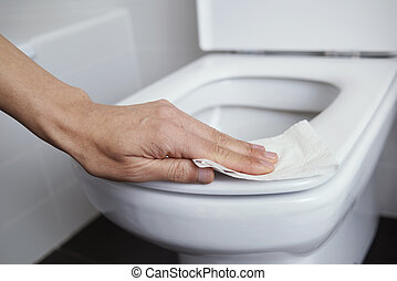 man cleaning the toilet seat with a piece of paper