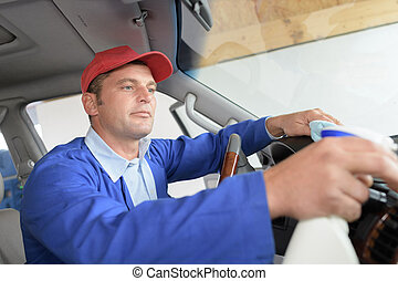 Man cleaning vehicle cab