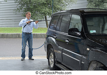 Man cleaning vehicle with pressure washer