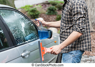Man cleaning window in a car