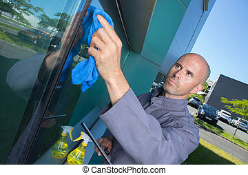 man cleaning window in his house