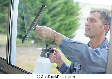 Man cleaning windows with squeegee
