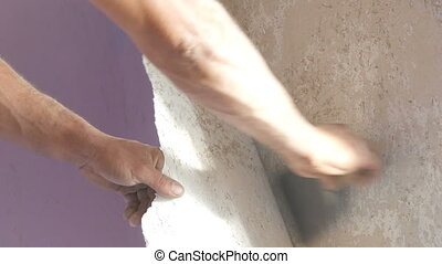 Man cleans or peels the wall from old wallpaper