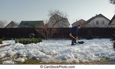 Man cleans snow in yard with shovel