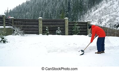 Man cleans snow with a shovel in the yard of his house