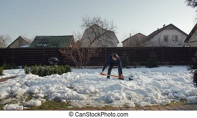 Man cleans snow with shovel in the yard