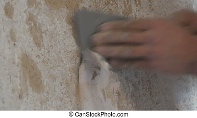 Man cleans the clay walls of old wallpaper with a spatula close up view