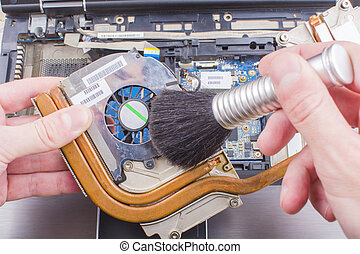 Man cleans the cooling system of the laptop cooler with a brush, close-up