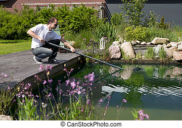 man cleanse his garden pond, mann reinigt seinen gartenteich...