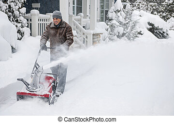 Man clearing driveway with snowblower - Man using snowblower...