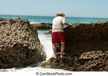 man climbed on a rock in the sea