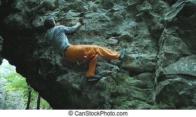 man climbing bouldering route on the cliff in the wood