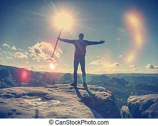 Man climbing hiking exploring silhouette in mountains sunset