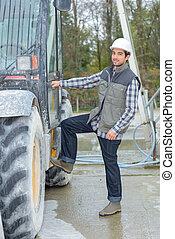 Man climbing into construction vehicle