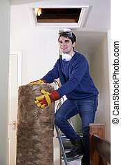 Man Climbing Into Loft To  Insulate House Roof