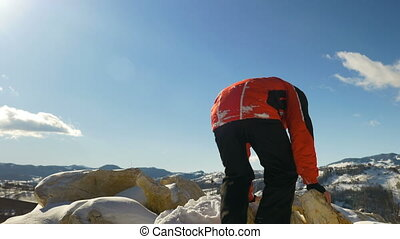 Man climbing on the top of a mountain cliff and celebrating...