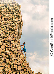 Challenge - Young man climbing the large pile of cut wooden logs