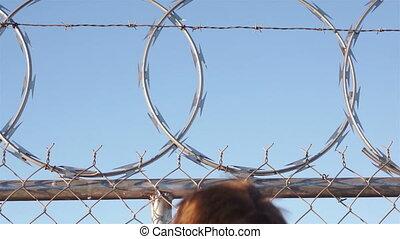 Man Climbing Razor Wire Fence