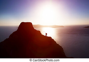 Man climbing up hill to reach the peak of the mountain over ocean.