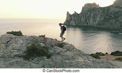 Man climbs the rocks and raises his hands - Man traveling...