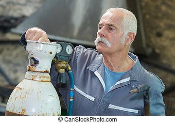 man close valve of pressure gauges on the oxygen tank