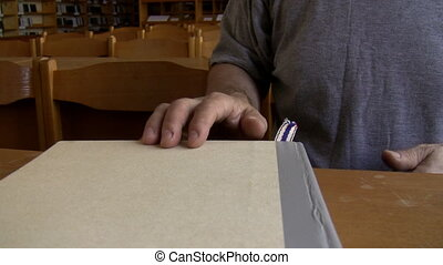 Man closes book and leaves library
