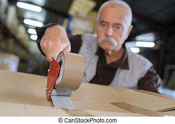 man closing cardboard box taped up