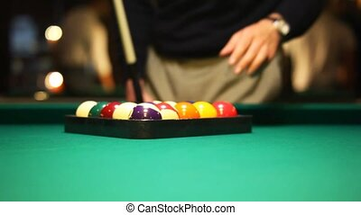 man collect balls in triangle on biliards table