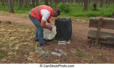 Man collecting plastic bottles around waste bin