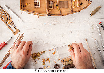 Man collects ship model on a white table horizontal