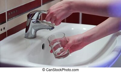 Man collects the water in a glass of tap water